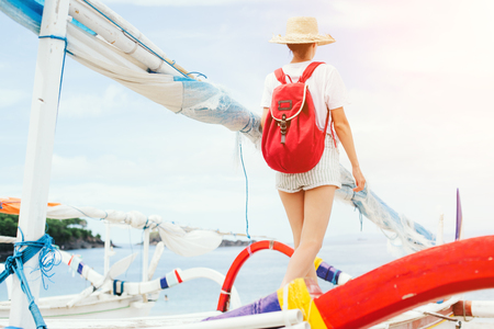 Young woman with hat and backpack walking at sailboat at sunny day Standard-Bild