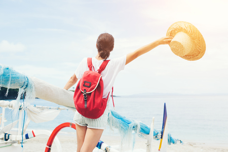 Young cheerful woman with outspread hand with hat and backpack on sailboat on beautiful island  Standard-Bild