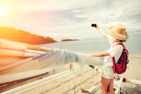 Young cheerful woman taking photo with mobile phone on beautiful island