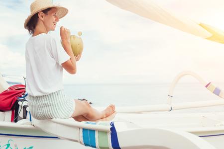 Young happy woman drinking fresh coconut juice sitting in boat near beach Stok Fotoğraf