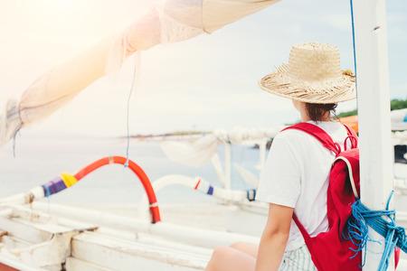 Young woman sitting at sailboat on beautiful island at sunny day