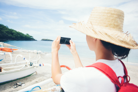 Young cheerful woman in hat taking photo with mobile phone on beautiful island