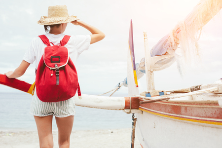 Young beautiful woman with backpack standing near sailboat on beautiful island  Standard-Bild