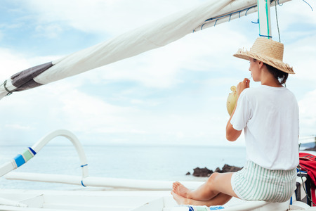 Young woman drinking fresh coconut juice sitting in boat near beach