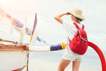 Young beautiful woman with backpack and hat standing near sailboat on beautiful island