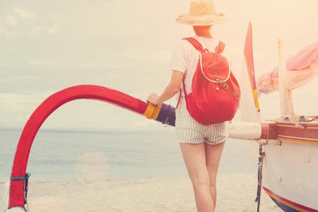 Young beautiful woman standing near sailboat on beautiful island
