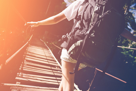 Young balancing woman with backpack traveling across hanging bridge in tropical forest, intentional vintage color and sun glare Standard-Bild