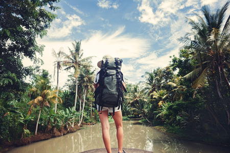 Woman with backpack standing near tropical river and looking far away