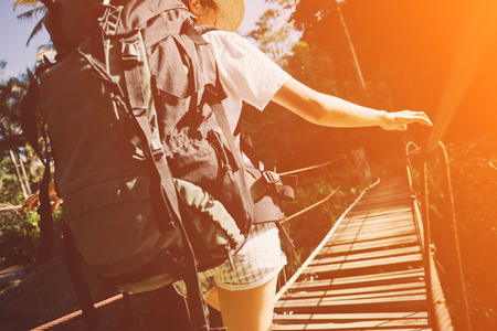 Young woman with backpack traveling across danger hanging bridge, intentional vintage color and sun glare