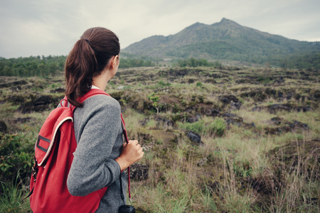 Woman traveler looking far away at the volcano