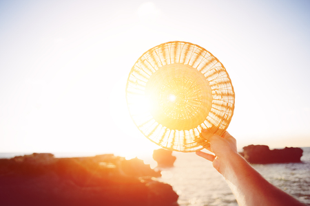 Straw hat in womans hand near the ocean, intentional sun glare and vintage color