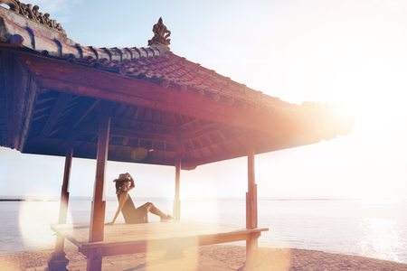 Young pretty woman relaxing in the sun shelter. Blurred effect, lens flares effect, intentional sun glare Stock Photo