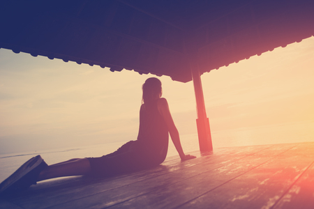 Silhouette of woman in yoga position, sun shelter near ocean. Intentional sun glare and vintage color