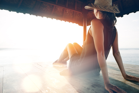 Young pretty woman resting near ocean. Blurred effect, lens flares effect, intentional sun glare Stock Photo