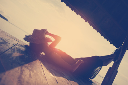 Young woman resting under sun shelter on the beach. Intentional sun glare and vintage color Stock Photo