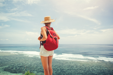 Young traveler with backpack and straw hat looking at the ocean