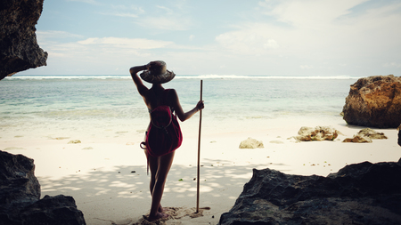 Young handsome woman on the beach with hat, stick and backpack