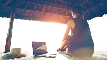 Freelancer sitting at sunset near the ocean with laptop. Blurry effect, lens flares effect, intentional sun glare,vintage color Stock Photo