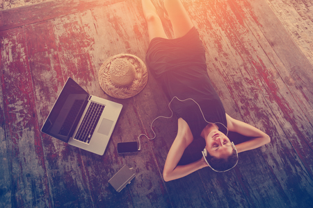 Young woman in dress resting and listening music with headphones. Intentional sun glare and vintage color Stock Photo