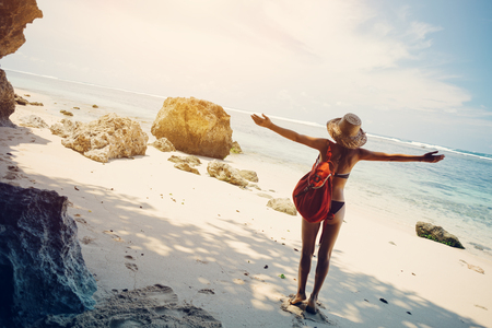 Young happy woman on the beach wearing swimming suit, hat and backpack