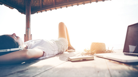 Young woman chilling with laptop and listening music with headphones near the ocean. Intentional sun glare and vintage color