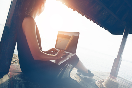 Woman working with laptop on the beach in shadow shelter. Blurry effect, lens flares effect, intentional sun glare Stock Photo