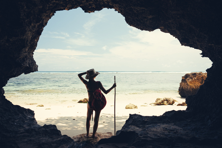 Silhouette of young woman standing in cave on the beach with hat, stick and backpack