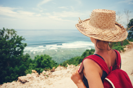 Traveling woman with straw hat looking at the ocean