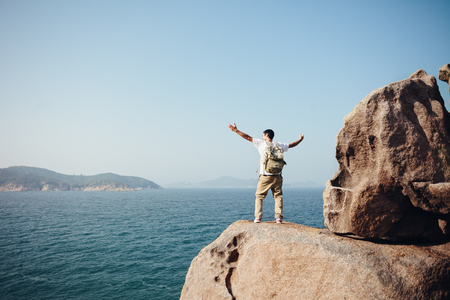 Cheerful traveler standing on the rocks near the ocean Stok Fotoğraf