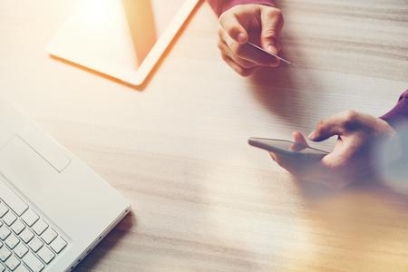 Carte de crédit et smartphone en mains. Ordinateur portable et tablette sur la table. Achats sur le Web., Éblouissement intentionnel du soleil et éclats d'objectif