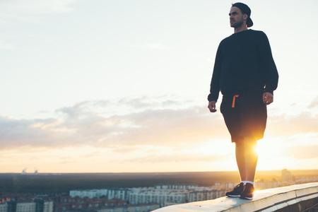 Brave man standing on the edge of the roof at sunset, outdoors