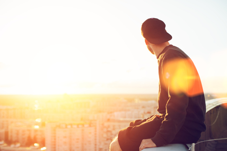 Young and brave man sitting on the edge of the roof and looking far away at the city, lens flares Reklamní fotografie