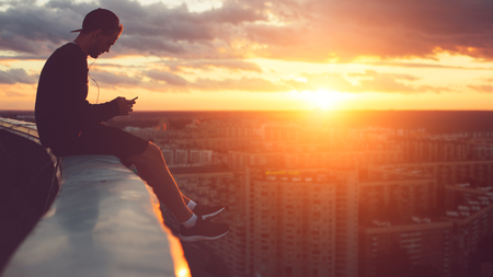 Young risky man chilling above the city with smartphone at sunset, outdoors