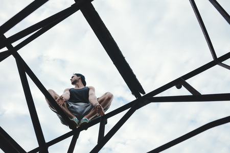 Young guy balancing and sitting on high metal construction, outdoors Stok Fotoğraf