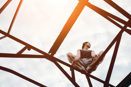 Risky man sitting on high metal construction, outdoors Stok Fotoğraf