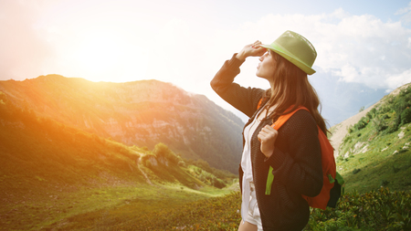 Woman traveling along mountain meadows. With small backpack and sun hat. Evening with sunset, outdoors