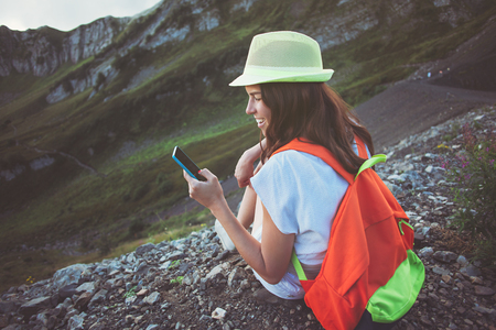 Cheerful woman with backpack and mobile phone traveling in mountains. Beautiful meadows touristic path. Digital communication. Texting with friends in social network, outdoors