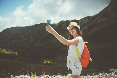 Young woman with backpack taking selfie photo with mobile phone. High mountains touristic path, outdoors Stok Fotoğraf