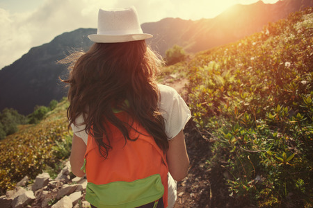 Young woman with waving long hair and backpack traveling along beautiful mountain meadows in the evening, outdoors Stok Fotoğraf