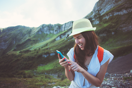 Cheerful smiling woman with mobile phone. Beautiful mountain meadows touristic path. Digital communication. Texting with friends in social network, outdoors