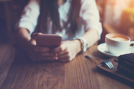 Close-up of mobile phone in womans hands, sitting in cafe with cup of coffee and cake, indoors