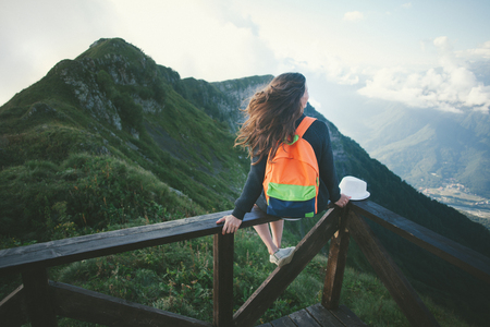 Young woman with backpack sitting high on the top of the mountain with hat and waving hair, outdoors Stock Photo