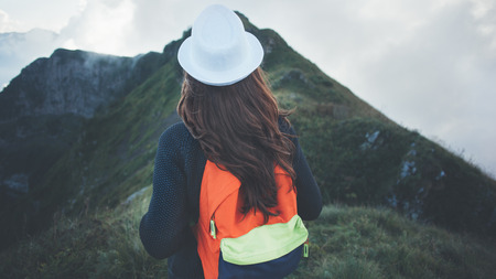 Traveling woman with bright backpack and white hat looking at foggy mountain at cloudy day, outdoors