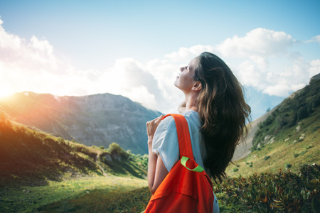 Beautiful woman traveling in mountain meadows. With small backpack and long weaving hair. Evening with sunset, outdoors Stok Fotoğraf