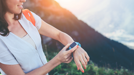 Young smiling woman adjusting smart watches on her wrist, while trekking and walking along mountain meadows, outdoors