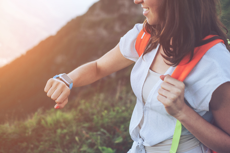 Smiling woman looking at smart watches on her wrist, while trekking and walking along mountain meadows, outdoors