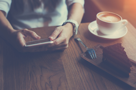 Close-up of mobile phone in womans hands typing message, sitting in cafe with cup of coffee and cake, indoors