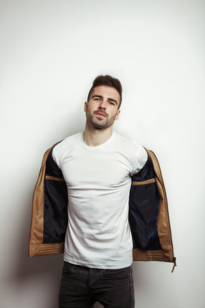 Handsome man in blank t-shirt taking off his leather jacket, empty studio wall background, studio indoors