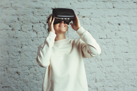 Handsome young woman wearing virtual headset. Smiling hipster using VR glasses. Blank sweater. White bricks wall background, studio indoors Stok Fotoğraf