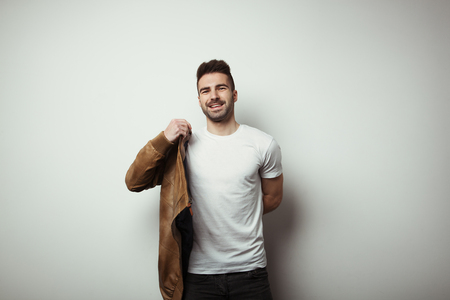Smiling man in blank t-shirt and jacket, empty wall in studio background, studio indoors